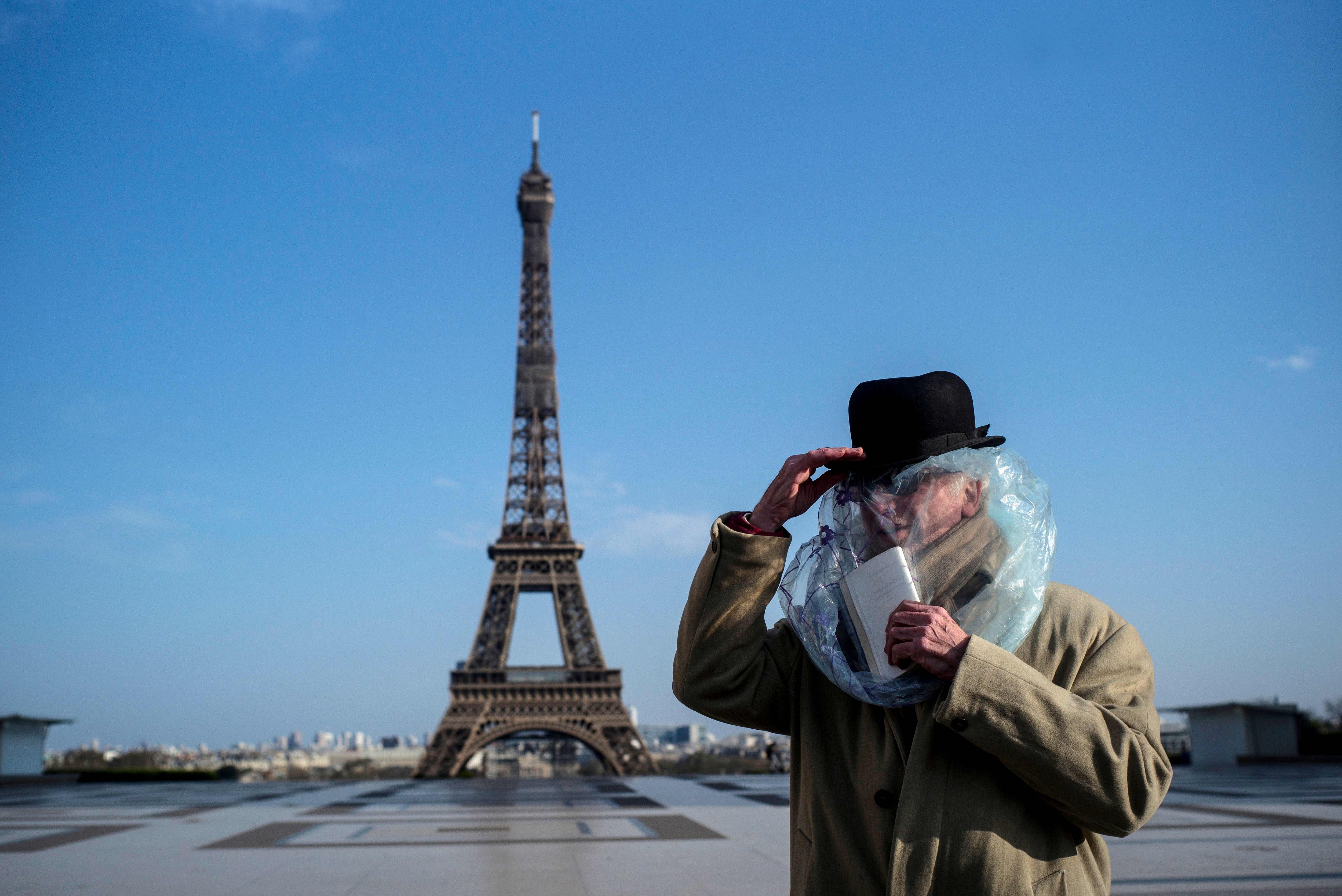 A man covered with a plastic bag for protection reads a book in front of the Eiffel Tower in Paris, France