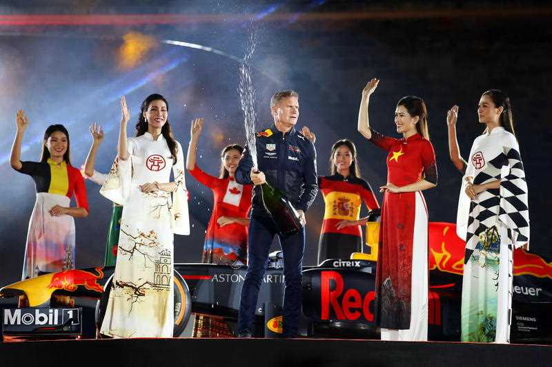 Former British Formula One driver David Coulthard (C) is flanked by Vietnamese models wearing traditional dresses during a ceremony in Hanoi, Vietnam