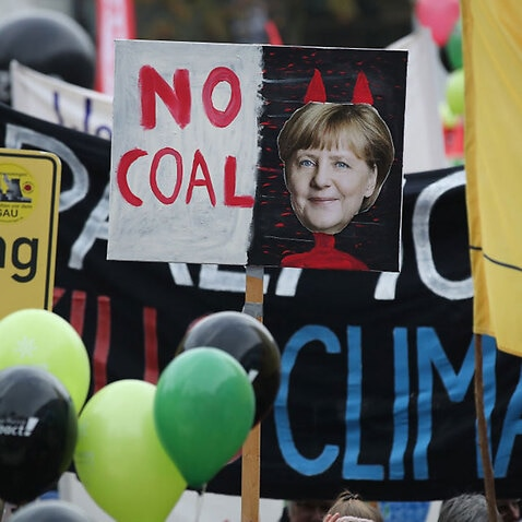 Activists hold up banners, including one that shows German Chancellor Angela Merkel with devil horns, at a protest march to demonstrate against coal energy.
