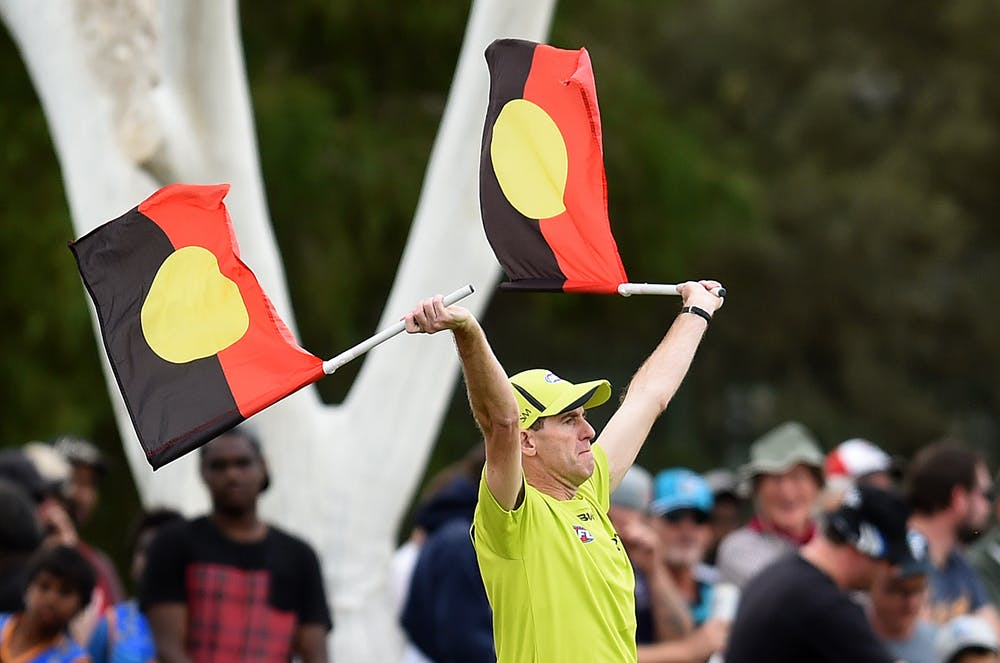 A goal umpire uses Aboriginal flags to signal a goal during a football match in Alice Springs in 2016.