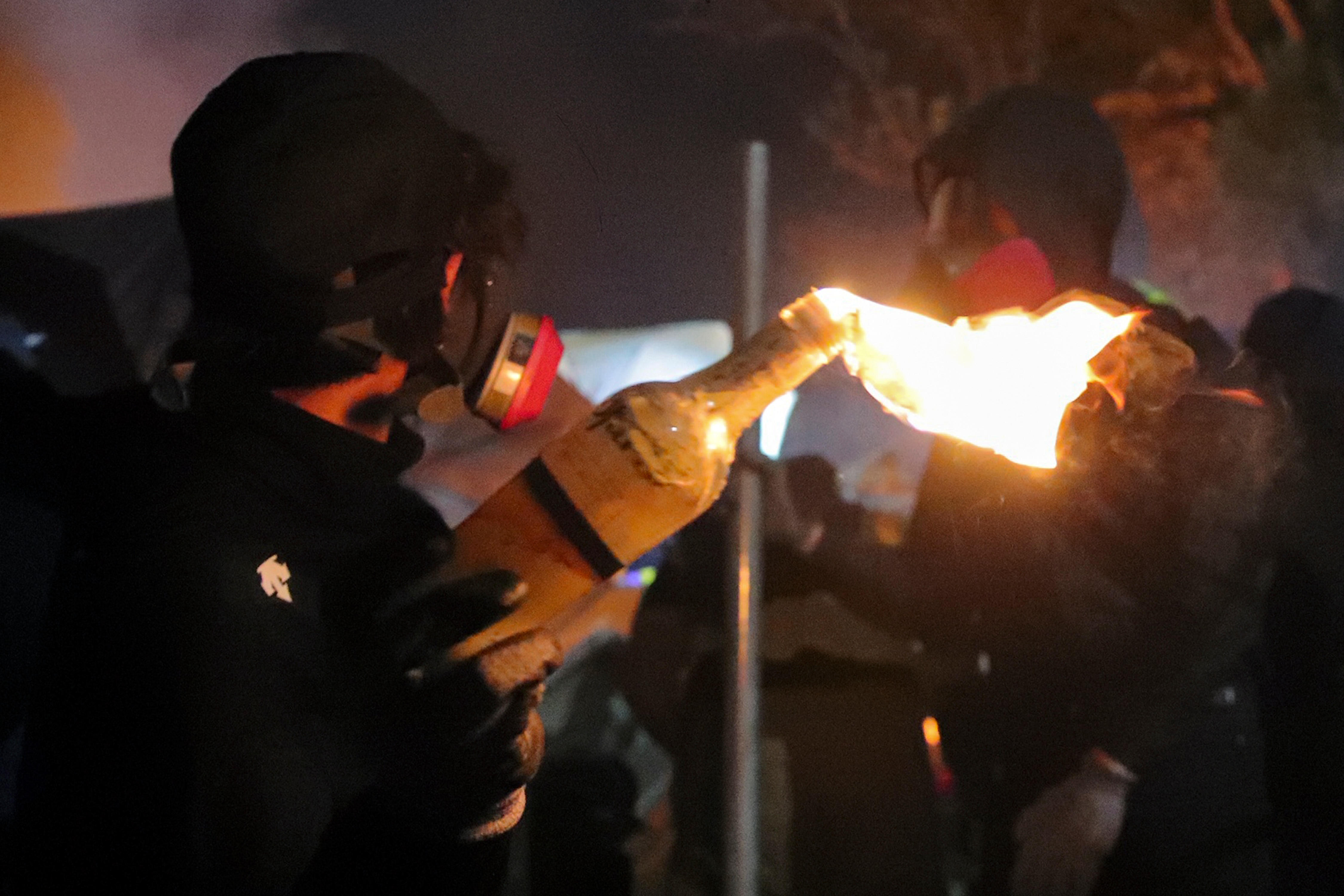 A student holds a molotov cocktail during clashes at the Chinese University.