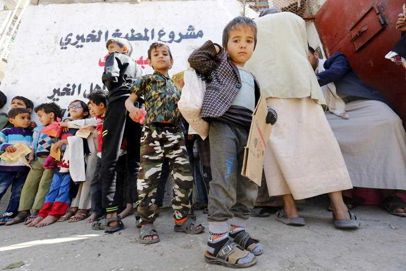 Conflict-affected children wait to receive their families' free food rations from a local charity in Sana'a, Yemen.