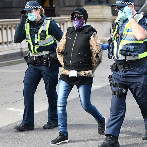 A woman is detained during an anti-mask and lockdown protest in Melbourne.