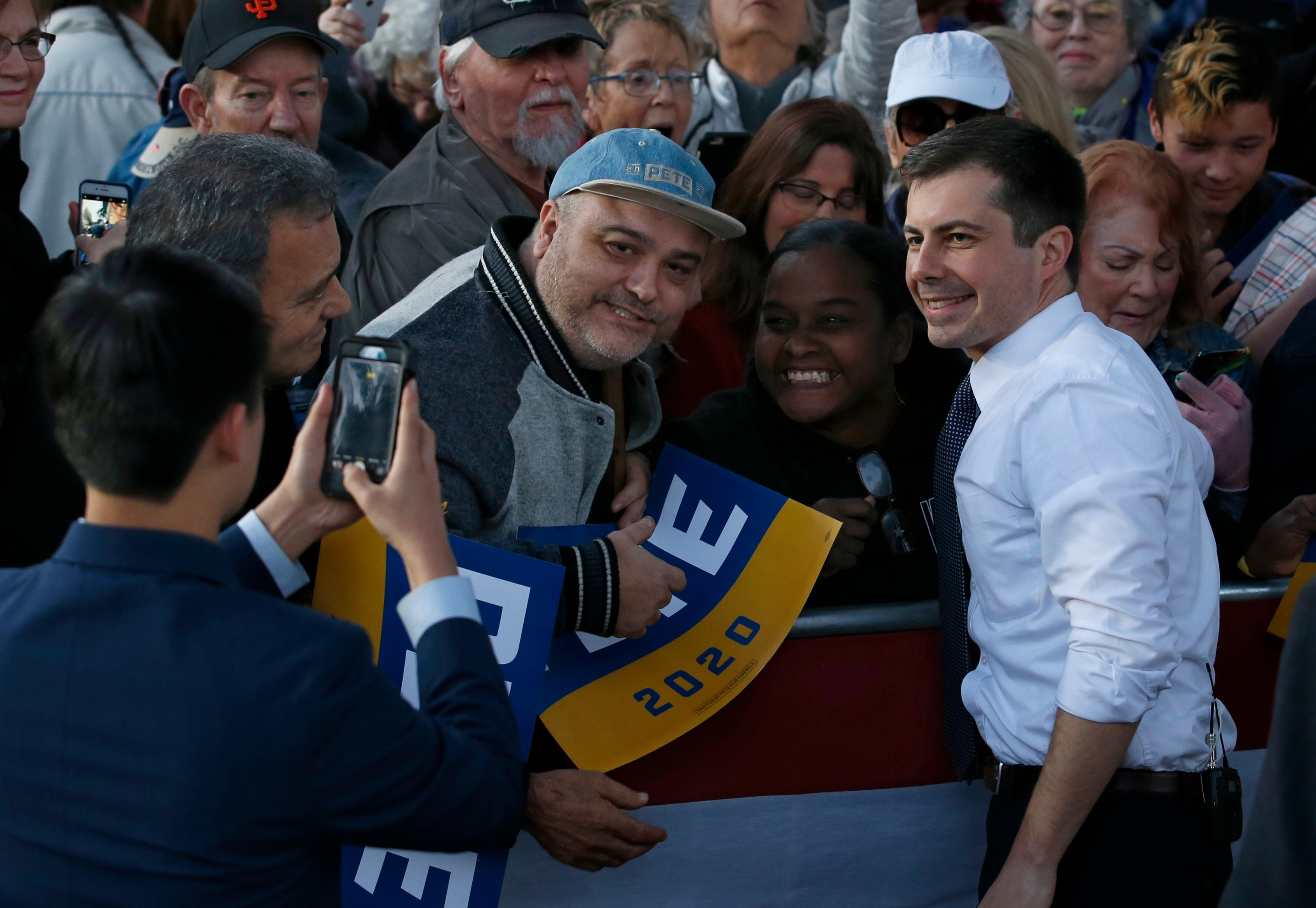 Democratic presidential candidate and former South Bend Mayor Pete Buttigieg poses for photos with supporters during a town hall rally in Sacramento, Californa.