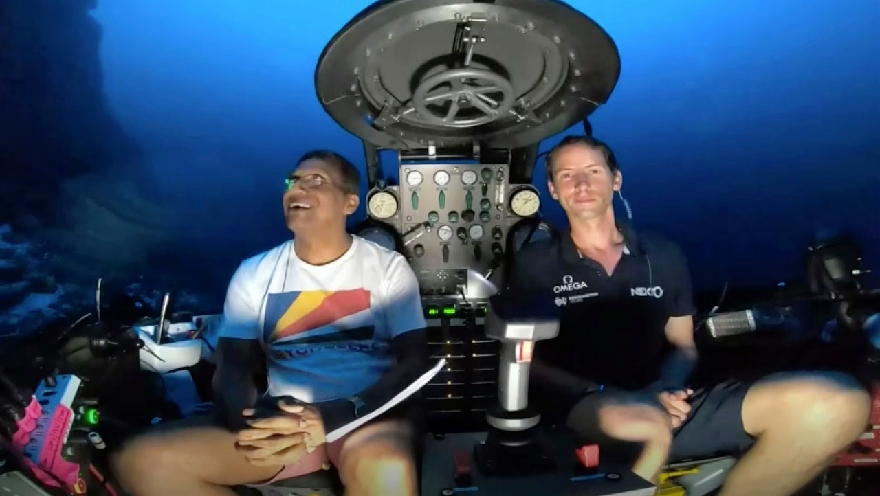 An image taken from video issued by Nekton shows Seychelles President Danny Faure, left, smiling after speaking from inside a submersible.