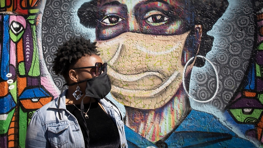 A Soweto resident in front of artwork educating residents about the dangers of COVID-19.