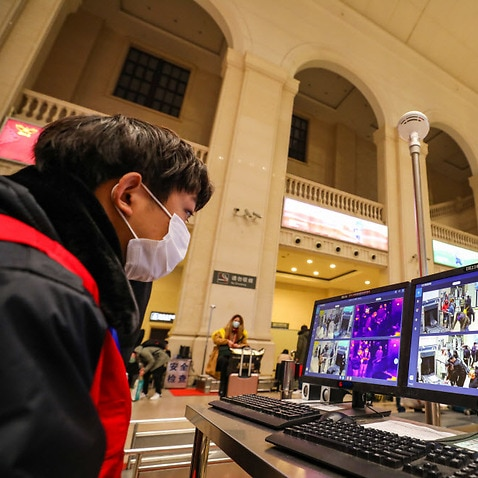 A worker monitors screens for fever signs on passengers detected by infrared detectors at Hankou Railway Station in Wuhan