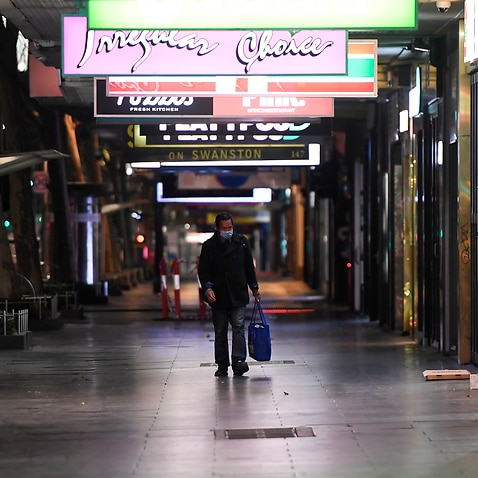 A man walks down Swanston Street after a citywide curfew is introduced in Melbourne.
