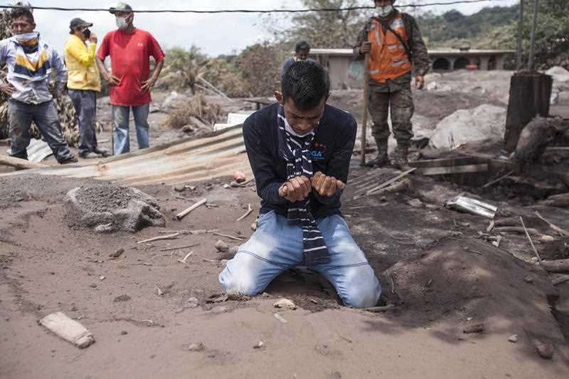 """Bryan Rivera cries after looking at the remains of his house, after his family went missing during the Volcan de Fuego or """"Volcano of Fire"""" eruption."""