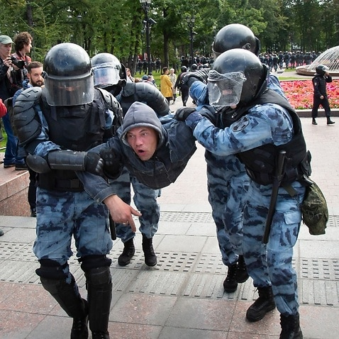 Police officers detain a protestor, during an unsanctioned rally in the center of Moscow, Russia, Saturday, Aug. 3, 2019.