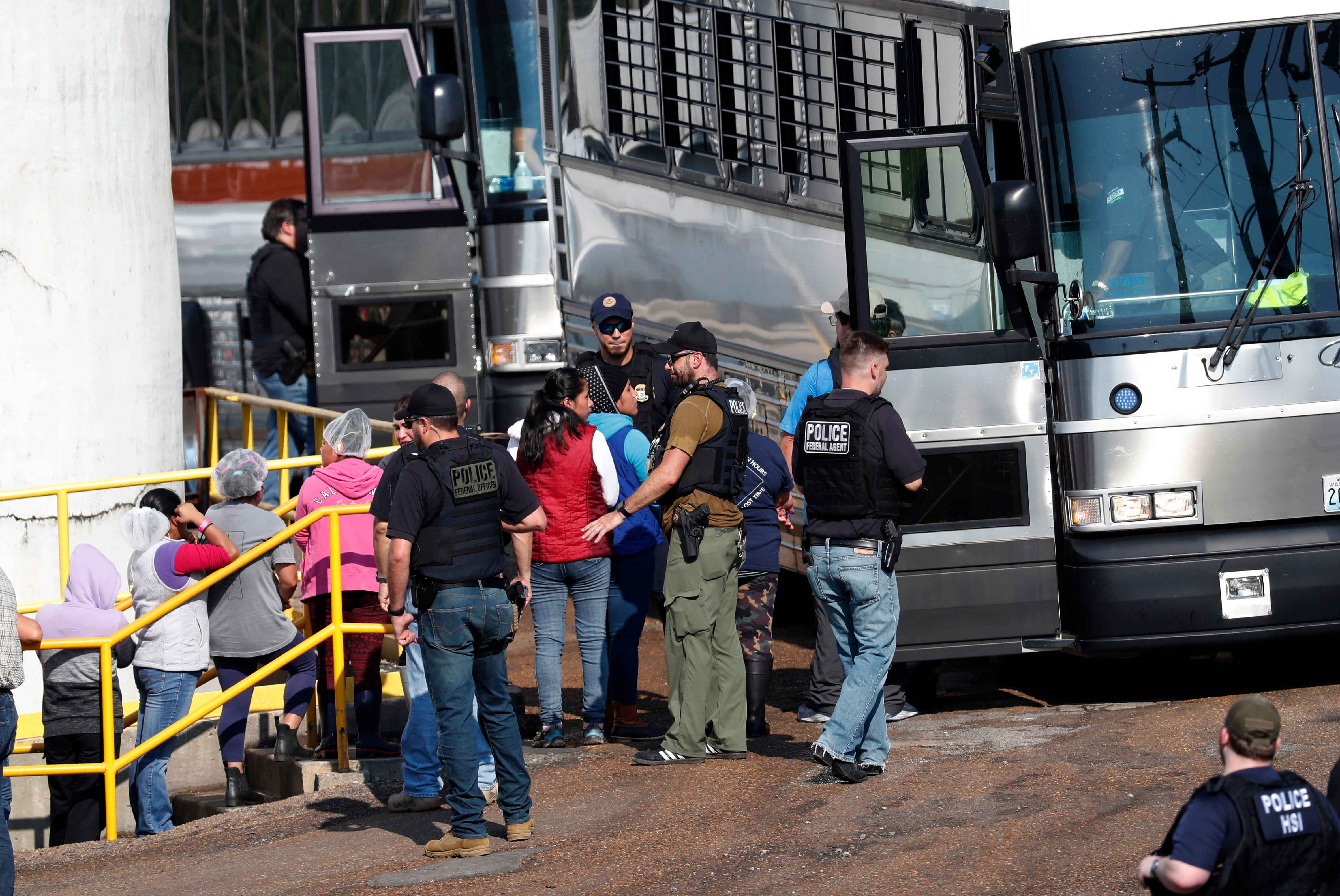 Handcuffed female workers begin to climb into a bus for transportation to a processing center following the raid.