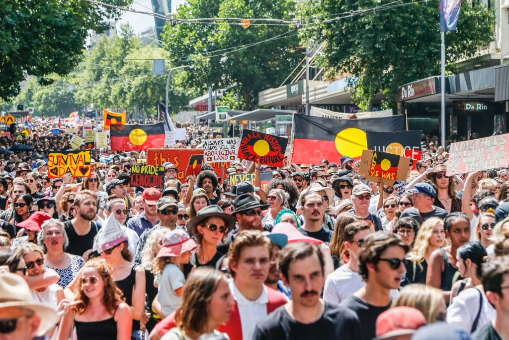A general view of protestors marching holding placards and shouting chants during a protest by Aboriginal rights activist on Australia Day in Melbourne.