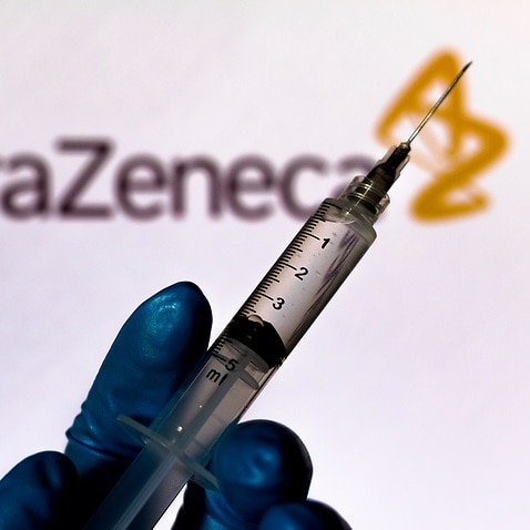 medical syringe is seen with AstraZeneca company logo