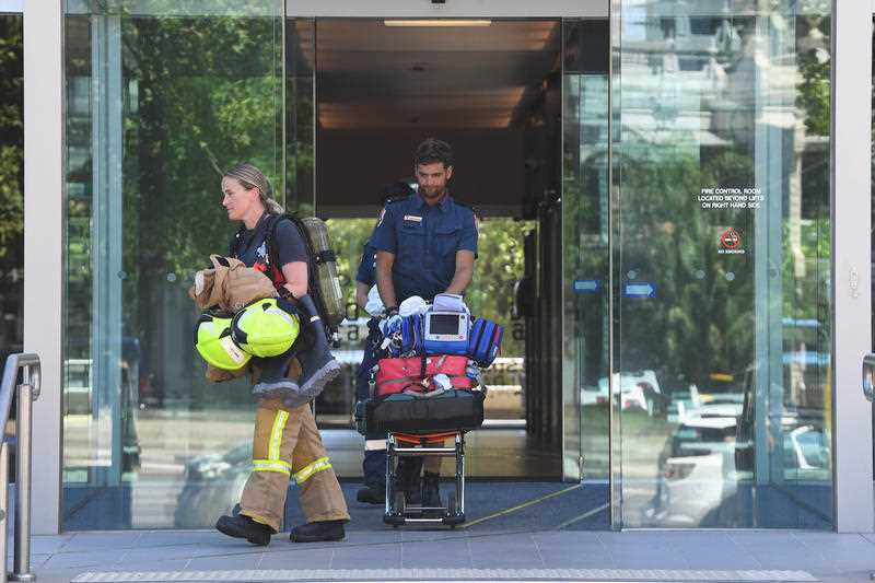 Emergency service personal exiting the building where the Korean consulate is located in Melbourne.