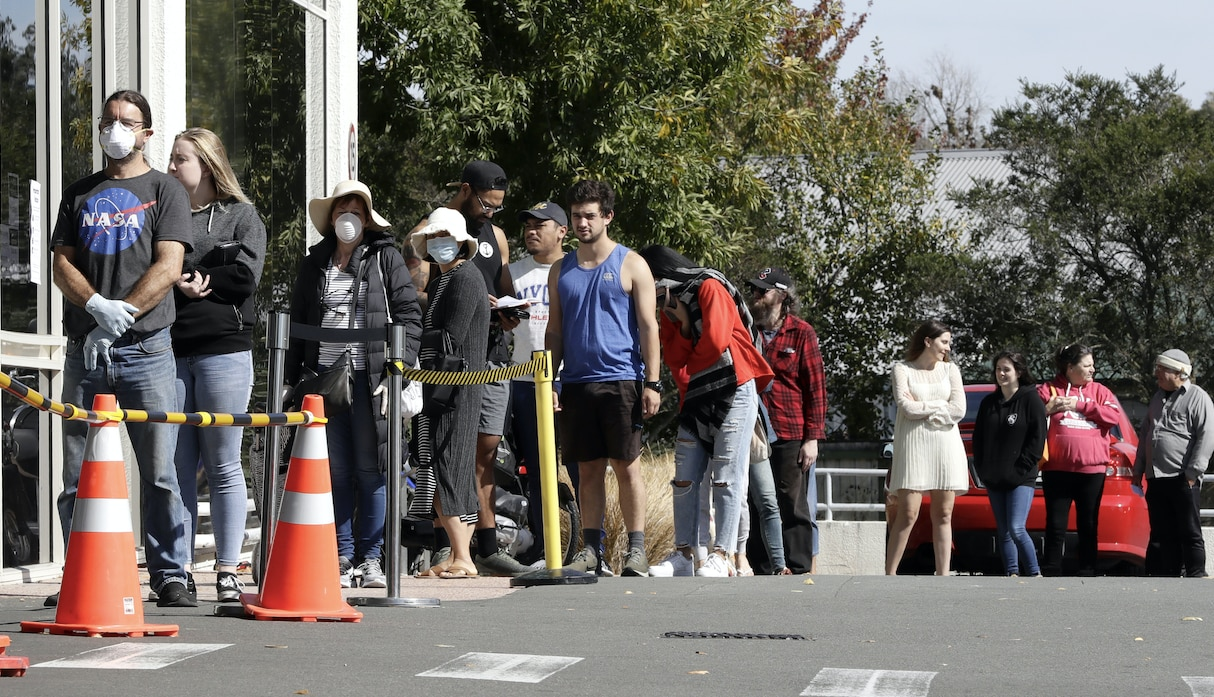 Customers queue to enter a supermarket in Christchurch.