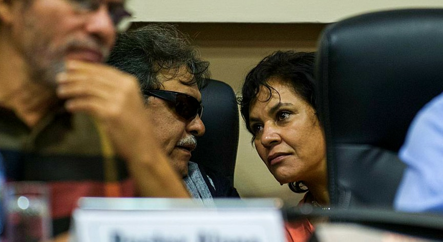 two FARC negotiators in discussion during a press conference.