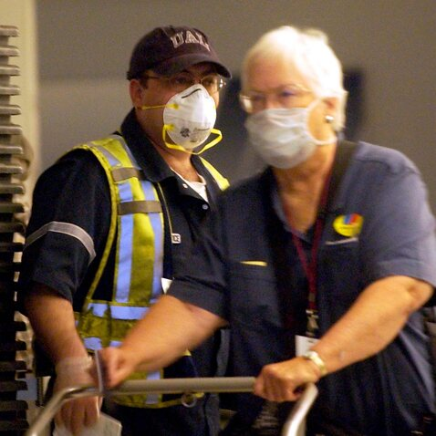 A  United Airlines employee wears a surgical masks to protect himself from SARS as passengers arrive at O'Hare International Airport from Hong Kong in 2003.