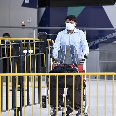 A passengers wearing facemasks arrives at Sydney International Airport.