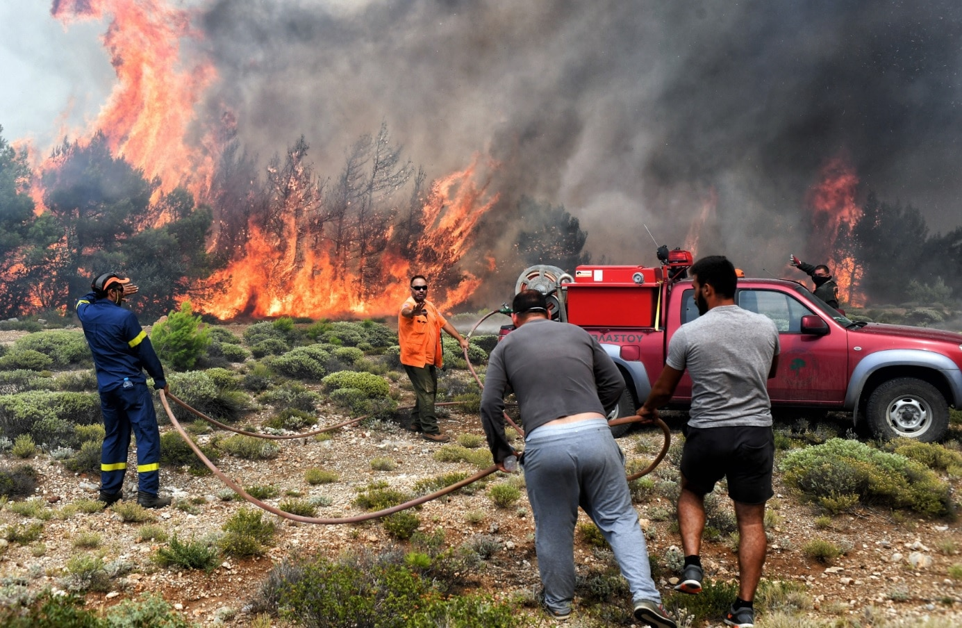 Firefighters and volunteers try to extinguish a wildfire raging in Verori, near Loutraki city, Peloponnese, southern Greece, 24 July 2018.