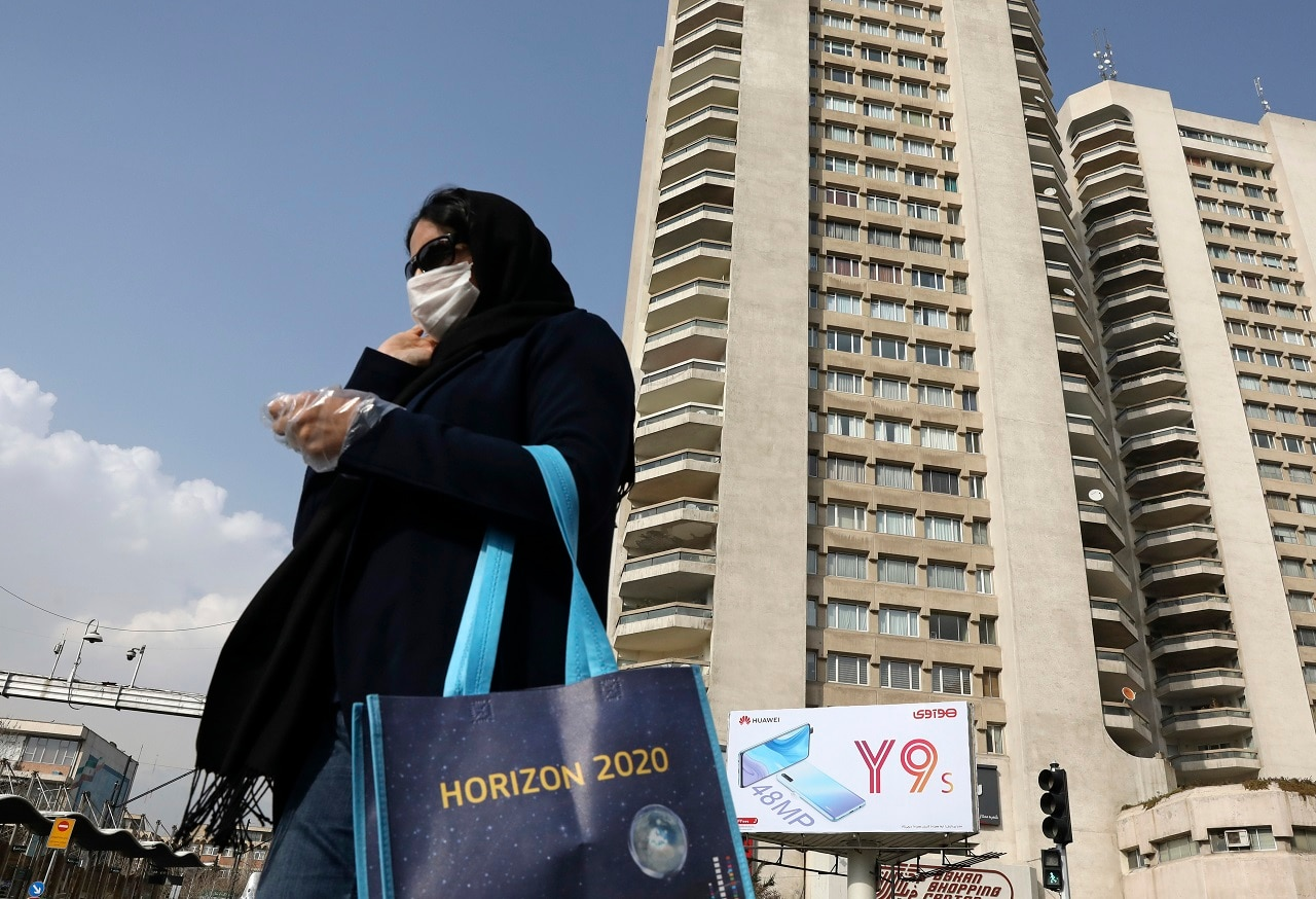 A pedestrian wearing a face mask crosses a street in northern Tehran.
