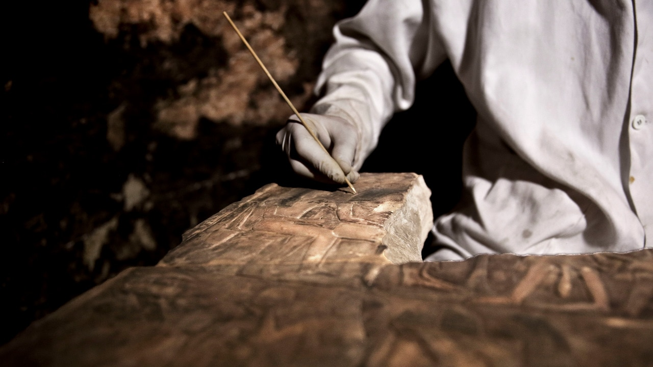 An archaeologists works on an artifact inside a tomb, at an ancient necropolis near Egypt's famed pyramids in Saqqara, Giza, Egypt.