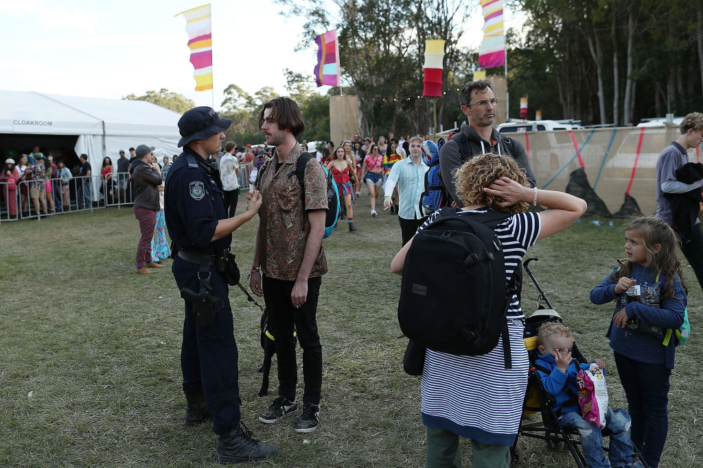 A police officer with a sniffer dog questions a Splendour in the Grass ticket holder in 2018.