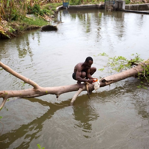 A man wash his cap in a river in Torbeck, a district of Les Cayes, Haiti. Tuesday Oct. 18, 2016.
