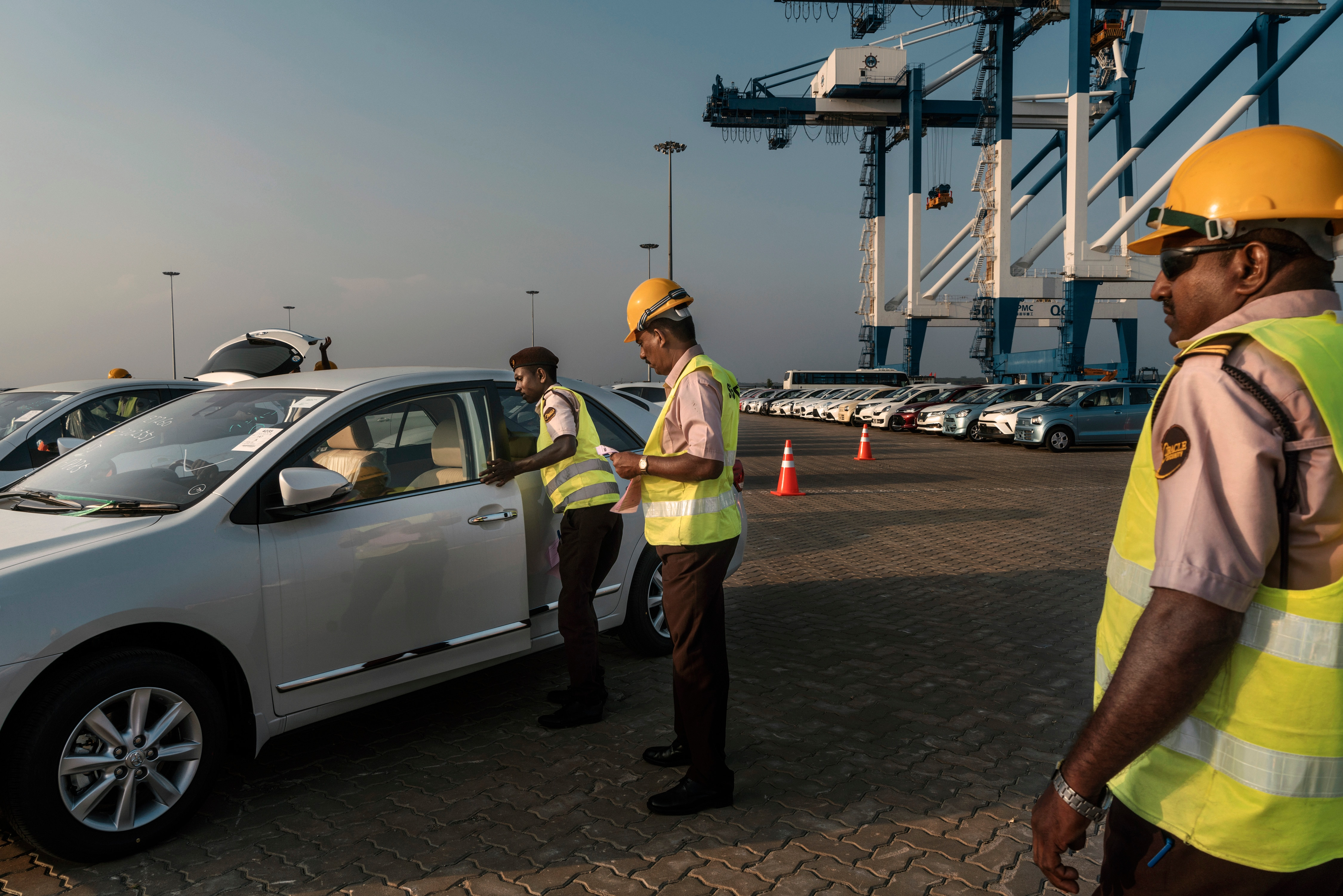 Sri Lankan workers process cars being unloaded from a ship at the Hambantota Port in Hambantota, Sri Lanka, March 5, 2018.